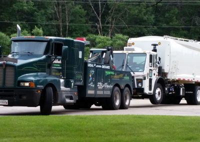 unit1-towing-new-garbage-truck-to-owner